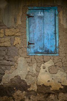 Blue window shutters, clay wall; Ghana
