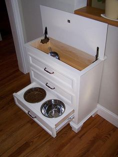Made from small dresser. Food is kept in top w/scoop. Drawers hold all pet supplies, leash, collar, sprays, etc.