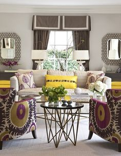 living rooms - Donghia Suzani in Pink Passion accent chairs gray walls chocolate brown silk valance white ribbon trim chocolate brown silk drapes canary yellow ottomans nailhead trim ivory sofa brass mirror top coffee tables black round marble top accordion accent table
