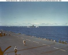 USS South Dakota (BB-57) steaming near USS Cowpens (CVL-25) as part of Task Group 58.3, during raids on the Marshall Islands, circa. January 1944. Note Cowpens' flight deck barriers in the foreground and men at her port side 20 mm and 40 mm guns.
