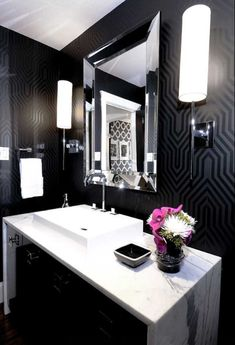 Marble sink top, a chrome framed mirror and decadent black wallpaper make this powder room sleek and sophisticated. Love it.