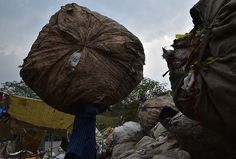 """A worker carries a bale of collected recyclable materials at a junk shop near the former dumpsite and landfill named """"Smokey Mountain"""" in Manila 