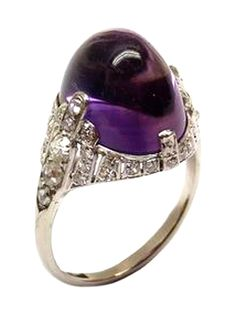 ART DECO CABOCHON AMETHYST AND DIAMOND RING, c.1925, This splendid example of Art Deco jewelry also shows a very modern evolution in jewelry aesthetics and reflects the bold under currents of the day. The oval cut cabochon amethyst to a tapered diamond set frame, formed by stepped vertical lines of rose and cushion cut diamonds, mounted in platinum Weight: 5g $8,000 #TresorsDuJour #AmethystDiamondRing #AntiqueJewelry #ArtDecoJewelry
