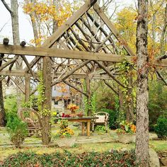 Enjoy a camp-inspired backyard getaway with a rustic structure. Bark-covered columns, branch trusses, and rough-hewn support beams create a woodsy pavilion that offers a central dining area flanked by alcoves for grilling and a buffet or cocktail bar.