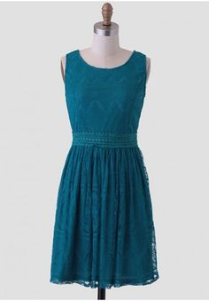 <p>Elegant and dramatic, this lovely teal dress is adorned with a delicate lace overlay with ornate detailing. Accented with crochet trim around the waist and a V-cut back, this dress can be paired with a jeweled necklace and metallic heels for a fancy dinner party. Hidden back zipper closure. Fully lined.</p> <p>Self: 100% Nylon<br /> Lining: 100% Polyester<br /> Imported<br /> 30.5