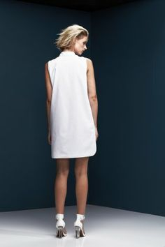 Sleeveless crisp white cotton shirtdress with concealed button placket.     the front panels are split into two separate but overlapping panels, that overlap from the waist to just above the hem.     back panel is lined in lightweight cotton, and finished with a curved hem.
