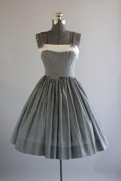 Deze jaren 1950 Pixie van Californië katoenen jurk is voorzien van een zwart-witprinter pastel print. Witte katoenen pique bovenste bodice die