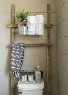"""She also made this reclaimed wood ladder as a way to utilize the space over the toilet for extra bathroom storage. """"This ladder was a super quick and easy DIY and cost just a few dollars,"""" writes Jenna Sue. """"Rather than buy a towel holder and add more holes in the wall, I simply draped a hand towel over the ladder rung and placed it within easy reach of the sink for guests."""""""