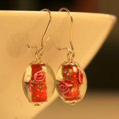 Punaisista lamppuhelmistä tehdyt korvakorut, joissa hopeanväriset koukut ja koristeosat.
