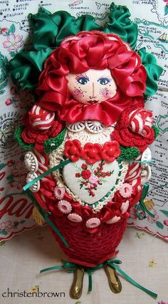 Lady Rose, is made from a base of felt, adorned with heart shaped motifs, ribbons and vintage buttons.