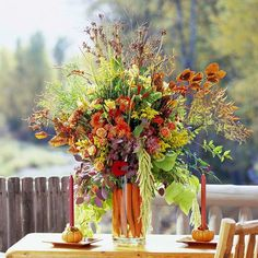 Vivid colors & tall vases create eye-catching centerpieces that last. Here, a few carrots are tucked around the exterior of the vase, while a dramatic combination of grasses and blooms add texture and vertical interest.
