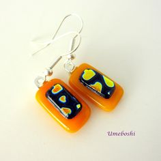 These cute handmade fused glass earrings have a sunny yellow base topped with a layer of partial dichroic glass hearts! The golden hearts float on a black base and are outlined with a delicate line of blue. The rectangular fused glass jewelry is colorful and happy and will catch the light nicely with just the right amount of sparkle. These earrings measure 1.75 inches (4.5 cm) from the top of the ear wires to the bottom of the dangling glass. The ear wires are sterling silver with tiny…