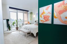 A deep green accent wall leads into a crisp white bedroom.
