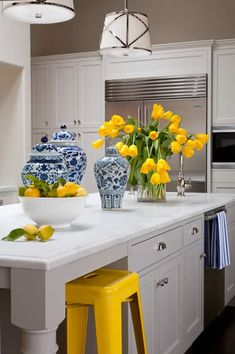 Stunning yellow and gray kitchen with wall of built-in cabinetry flanking a stainless steel refrigerator.