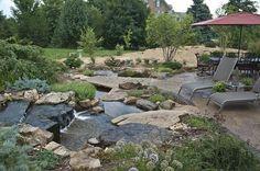 estanque de jardin que esta a niveles con rocas grandes