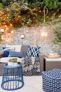 Stone outdoor space with blue patterned pillows and ottoman, neutral sofa, and hanging lights.