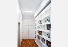 Uma estante de concreto, mais barata que uma de marcenaria, ocupa parte da parede do corredor e abriga a biblioteca da família. Projeto: Flavio Vila Nova