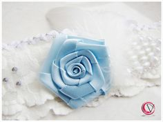 ivory color wedding garter with blue flower (rose), featrhers and pearls, source: http://www.vertigo.com.pl/projekty/podwiazki/#prettyphoto[gallery]/1/