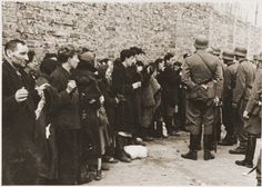 Jews captured by the SS during the Warsaw Ghetto Uprising are interrogated beside the ghetto wall before being sent to the Umschlagplatz. The original German caption reads: Search and Interrogation. Photo credit: Poland National Archives