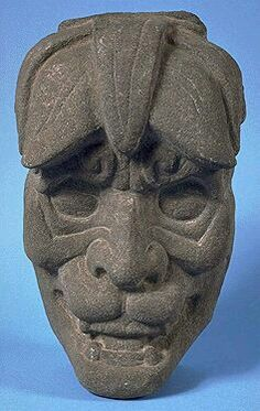 This mask represents the Jaguar God, who first appeared in the Olmec culture as a were-jaguar. Flared nostrils, scrolled eyebrows, and pointed teeth are typical features of this deity. He is also the God of Rain and Lightning who lives in the Underworld. Maya kings and nobles wore jaguar skins and headdresses as a symbol of their elevated status.