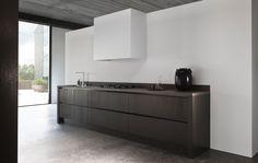 cocina abierta, muebles sin tiradores color carbón, campana de obra, suelo microcemento