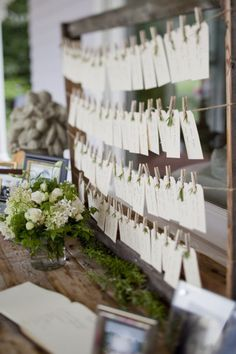© Mel & Co. table cards hanging in a picture frame on clothing line w/ clothing pins.