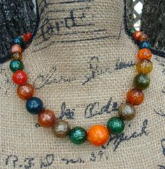 """Vintage Faux Glass look necklace. It is plastic beads that look like real glass. Very deep Earthy Colors. It has very pretty detailed gold fixings.It came from the 1950s era of fashion. It measures 21"""" clasp to clasp. Unique hook clasp."""
