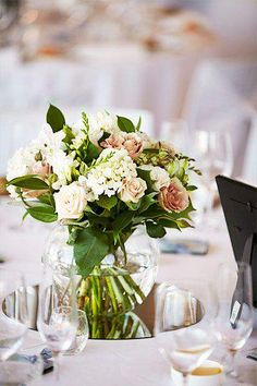 Floral table centrepieces displayed in fishbowl vases - Wedding Inspirations
