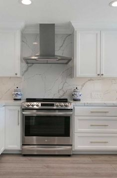 Both the countertops and the full-height backsplash were designed with a stunning marble-inspired Calcutta Laza Quartz slab. Kitchen Sink Design, Home Decor Kitchen, Kitchen Quartz Backsplash, Kitchen Renovation Inspiration, All White Kitchen, Transitional Kitchen, Updated Kitchen, Kirchen, Quartz Slab
