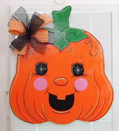 "Too cute! This adorable smiling Pumpkin Door Hanger is made of wood and is hand painted. This Halloween Door Hanger has been sealed and is safe for outdoor use. A wire is attached for quick and easy display. The bow is made with wire edge ribbon so that it can be fluffed back out when needed. This wood sign measures 22 by 26 tall.  Ribbons may vary but will always coordinate with the design.  Include ALL personalization info in the ""Note to Seller"" section during checkout. (Ex. names, dates…"