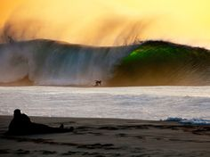 Picture of Tiago Gil surfing a wave at dusk, Pipeline, Hawaii