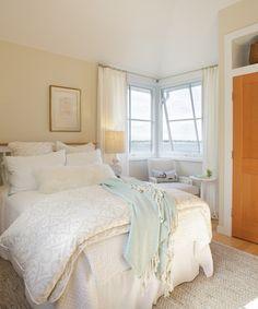 Acogedor dormitorio con ventanales en esquina vestidos con cortinas.