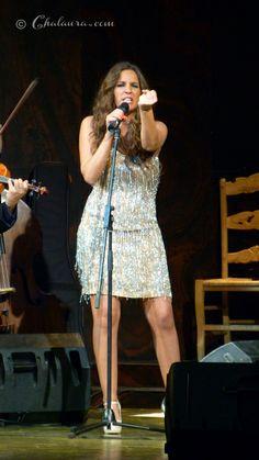 Bonita foto de Maria Toledo de pie frente al micro mientras canta con un puño cerrado lo que le da mucha fuerza al momento