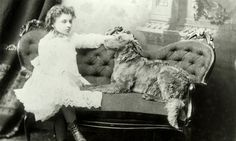 Circa 1888 black and white photograph of Helen Keller as a child, sitting on a couch, legs crossed. Her dog, Jumbo, is sitting next to her. She has one hand on its head.