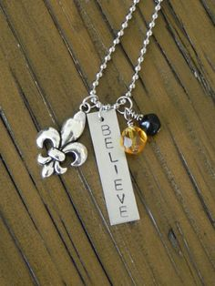 Who Dat ... New Orleans Saints... Charm Necklace with pewter fleur de lis... black and gold beads... hand stamped BELIEVE charm
