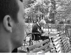 Boy - young man - teenager looking at an elderly man reading a newspaper, both sitting down on chairs, black & - Stock Image