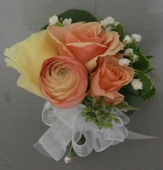 Corsage made of peach ranunculus, peach spray rose, babies breath, and butter yellow lisianthus by studio ag.