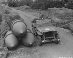 A member of the 2107th Ordnance-Ammunition Battalion inspects a store of 4,000-pound bombs, some under camouflage netting, along the roadside at the Sharnbrook Ordnance Depot in Bedfordshire, England (July 1943). Note how the Jeep shows the comparative size of the blockbuster munitions.