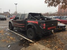 Customized Ford Raptor with tire racks in the bed