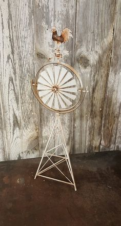 Unique old rustic metal toy or display wind mill with directions and rooster on top.  The fan blades do spin as well as the North South East and West but the rooster and large circular frame are stable.  The wind mill stands 24 tall and the base is a 7 triangle. This unique little windmill is a perfect accent for todays farm house urban look. I love the rust that peaks thru the chippy white paint.
