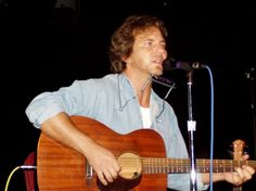 Eddie Vedder in a soft blue shirt. He sings...and he plays the guitar...