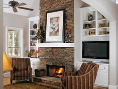 Cozy Comfort This stacked-stone, floor-to-ceiling fireplace comes alive against the crisp, white mantel and bookcases. The shades of the stone are repeated in the stripes of the chairs that flank the fireplace opening click now for info. Fireplace Built Ins, Fireplace Remodel, Brick Fireplace, Living Room With Fireplace, Fireplace Surrounds, My Living Room, Fireplace Ideas, Fireplace Bookshelves, Basement Fireplace
