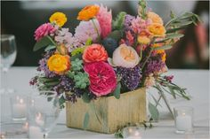 colorful and whimsical. peach garden rose, ranunculus, succulents, thistle.