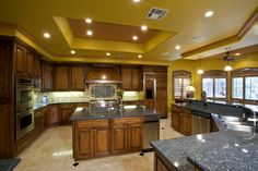 Yellow ceiling kitchen with rich wood cabinetry and two level granite countertop.