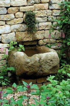 STONE TROUGH WATER FEATURE SET INTO DRY STONE WALL IN THE HERB SOCIETY'S GARDEN, CHELSEA 2003. GARDEN DESIGNED BY CHERYL WALLER  clivenichols.com