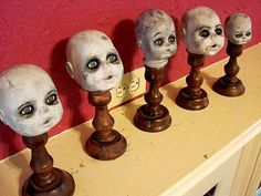 halloween decor inspiration -- easy diy baby doll zombie heads on display. would make great pathway markers with string lights stuck inside of them or behind them