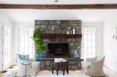 A cottage living room feels plush yet airy thanks to an embellishment of greenery on a stone-and-wood fireplace that brings elements of the outdoors in.