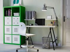 A home office with green KALLAX storage, LINNMON table in black and white and a white VÅGSBERG chair