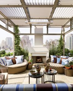 A modern rooftop terrace features a custom trellis and an outdoor fireplace.