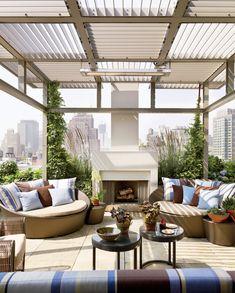 A modern rooftop terrace features a custom trellis and an outdoor fireplace.